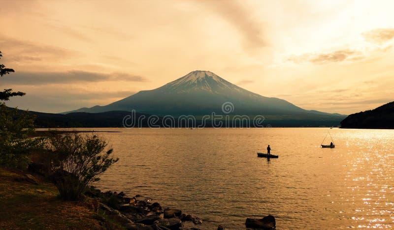 Fritids- sportfiskarekontur som framme fiskar av Mount Fuji på skymning fotografering för bildbyråer
