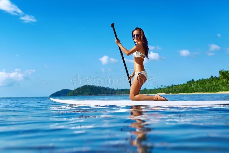 Fritids- vattensportar Kvinna som paddlar på bränningbräde Sommar arkivbild