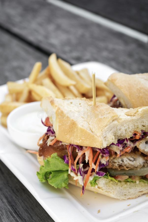 Fritou o sanduíche golpeado da faixa de peixes frescos com batatas fritas da salada da salada de repolho e molho de tártaro fotografia de stock