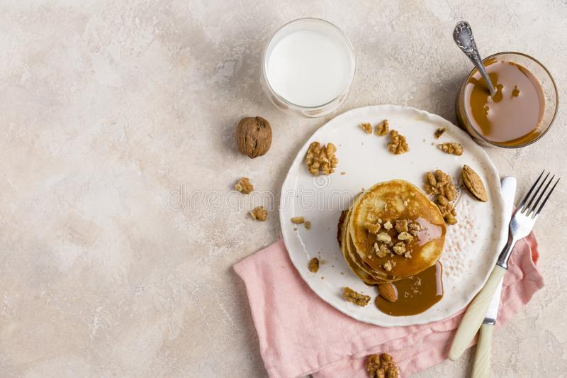 Fritt utrymme med bunten av pannkakor med karamell och muttrar på den vita plattan på vit bakgrund royaltyfri fotografi