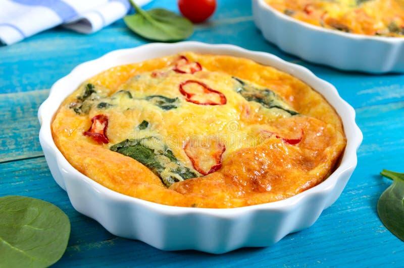 Frittata com legumes frescos e espinafres Omeleta italiana em formulários cerâmicos fotos de stock
