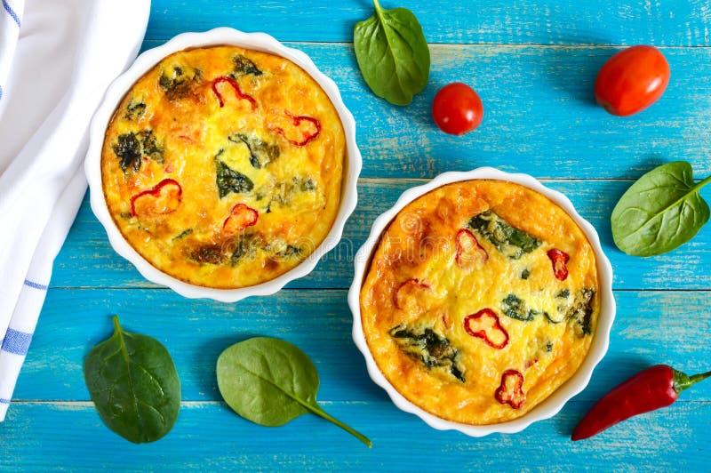 Frittata com legumes frescos e espinafres Omeleta italiana em formulários cerâmicos imagens de stock