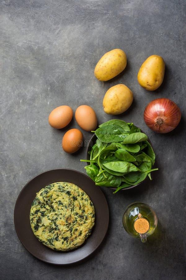 Frittata délicieux fait maison avec des épinards de plat Huile d'olive d'oeufs de pommes de terre d'ingrédients de recette à l'ar photos libres de droits