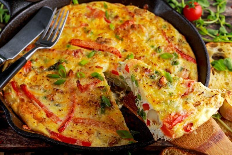Frittata fait d'oeufs, pomme de terre, lard, paprika, persil, pois, oignon, fromage dans la casserole de fer Sur la table en bois photo libre de droits