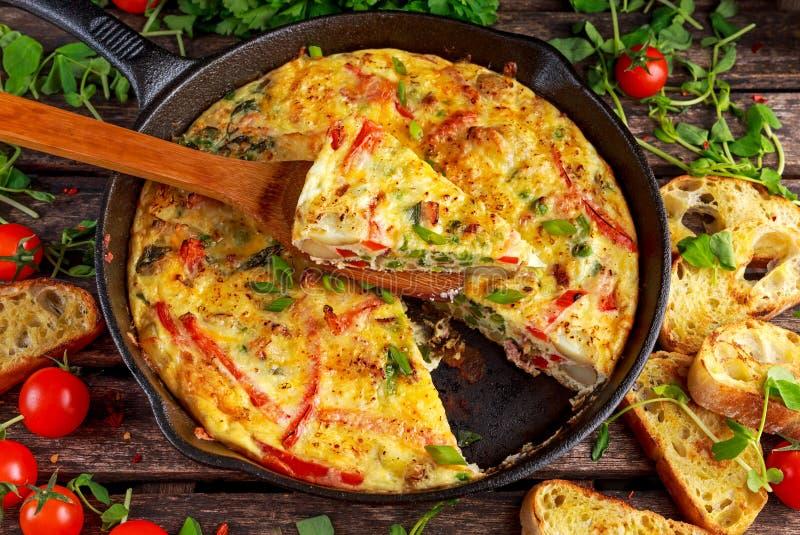 Frittata fait d'oeufs, pomme de terre, lard, paprika, persil, pois, oignon, fromage dans la casserole de fer Sur la table en bois image libre de droits