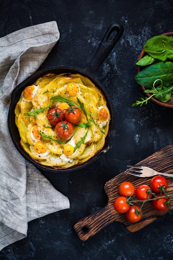 Frittata met aardappels, spinazie, tomaten en kaas stock afbeelding