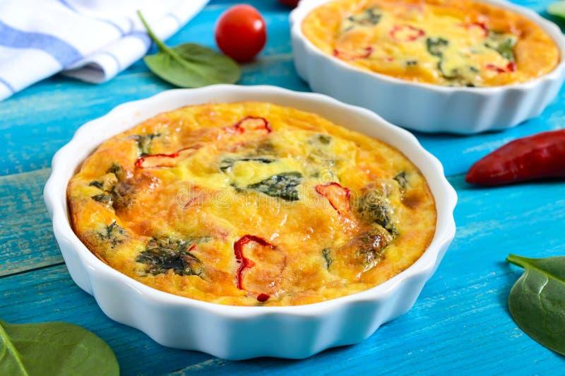 Frittata met verse groenten en spinazie Italiaanse omelet in ceramische vormen royalty-vrije stock fotografie