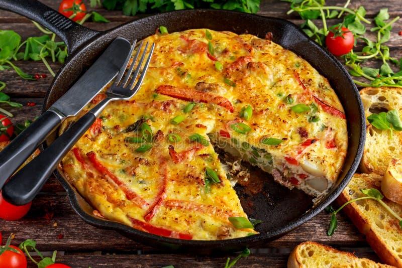 Frittata robić jajka, grula, bekon, papryka, pietruszka, zieleni grochy, cebula, ser w żelaznej niecce głębii pola płycizny stół  obrazy royalty free