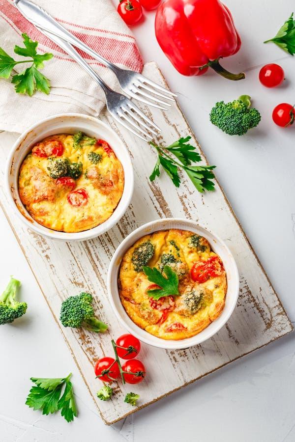 Frittata vegetal con bróculi, paprika rojo y la cebolla roja en sartén del arrabio  Visi?n desde arriba foto de archivo