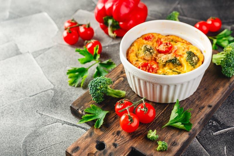 Frittata vegetal con bróculi, paprika rojo y la cebolla roja en sartén del arrabio  Visi?n desde arriba fotos de archivo