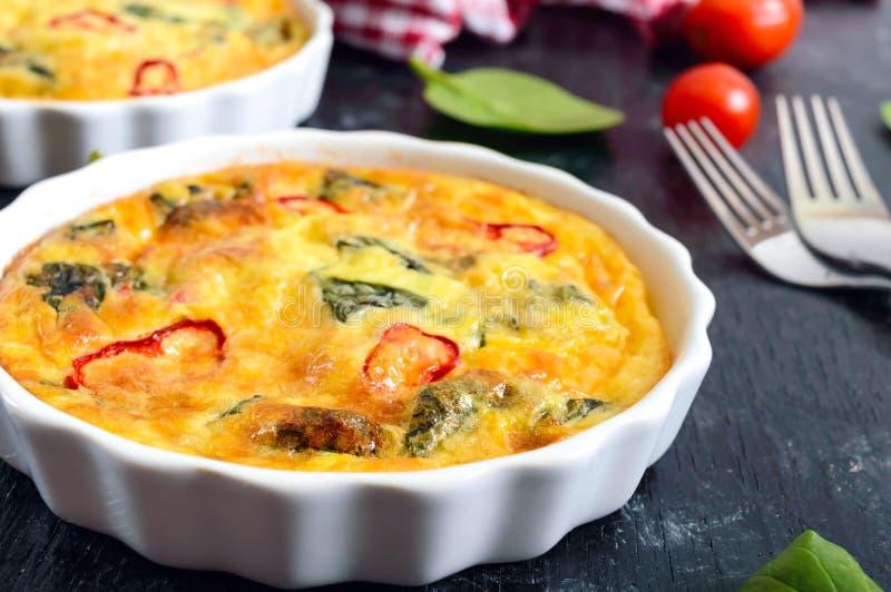 Frittata z świeżymi warzywami i szpinakami Włoski omlet w ceramicznych formach na czarnym tle zdjęcia stock