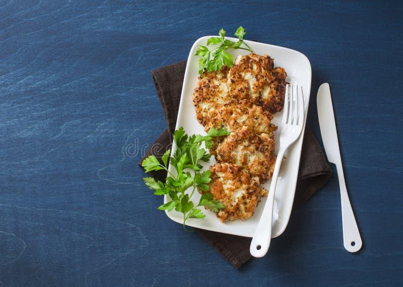 Frittelle del pollo e del cavolfiore su un fondo blu, vista superiore Antipasto squisito fotografie stock