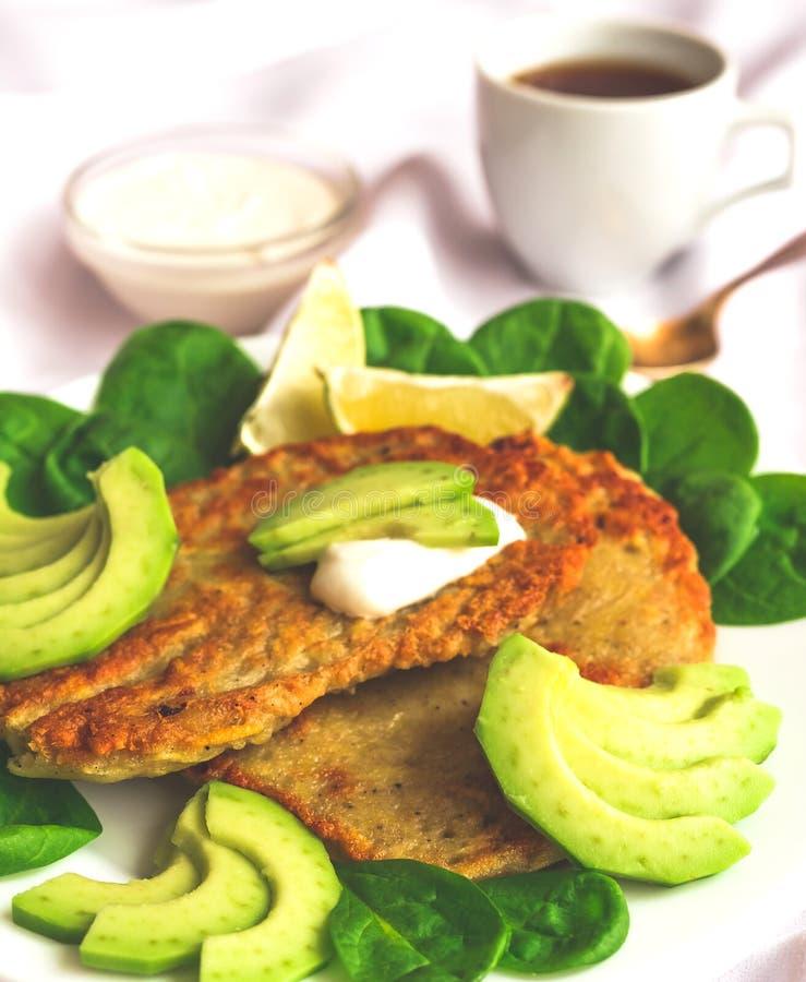 Frittelle della patata con l'avocado, gli spinaci e la calce affettati fotografia stock libera da diritti