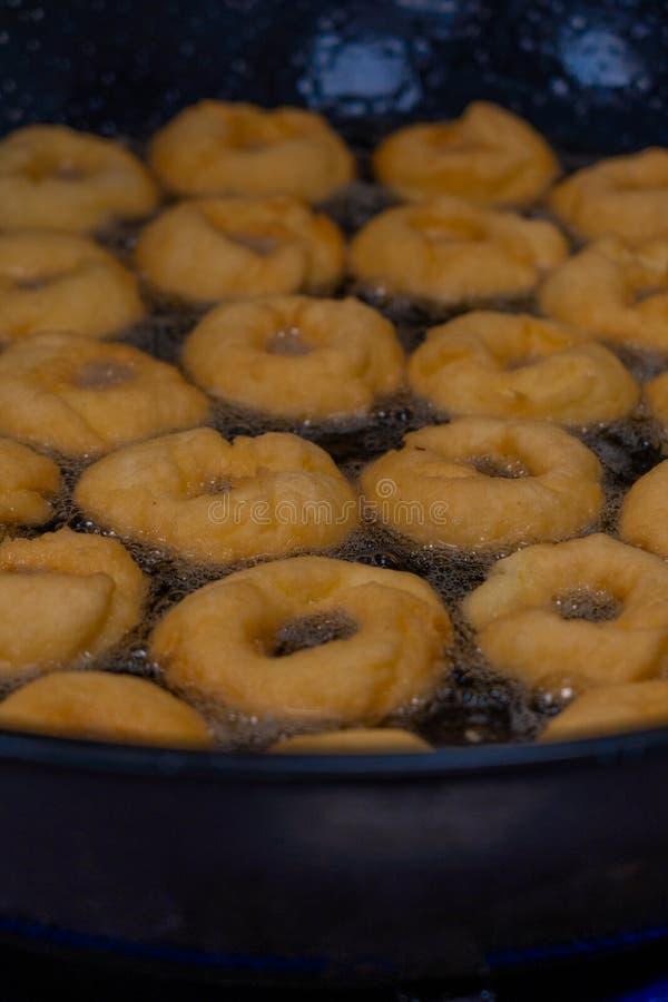 Fritter Donuts που κάνει τη μηχανή, τα χειροποίητα, τηγανίζοντας γλυκά και νόστιμα donuts στο καυτό πετρέλαιο σε ένα τηγάνι στοκ εικόνα με δικαίωμα ελεύθερης χρήσης