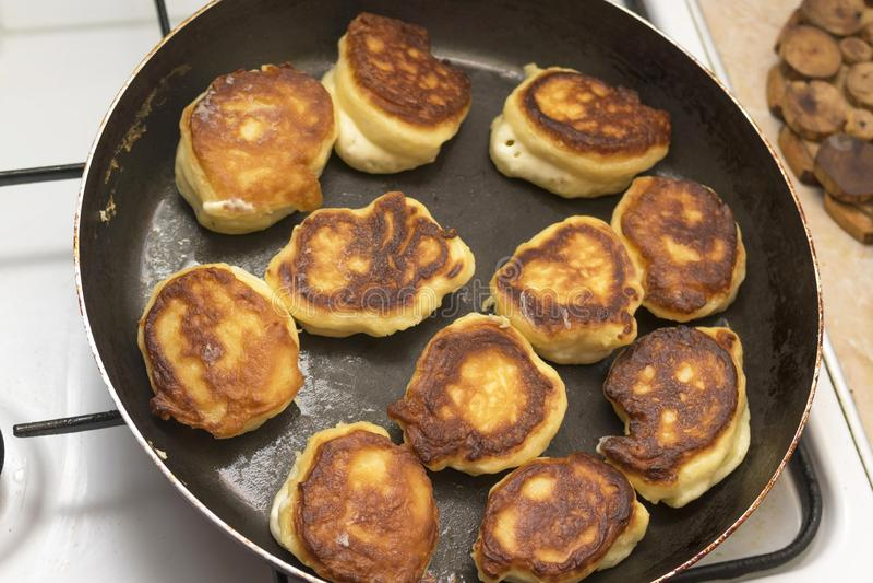 Fritters ή οι μπουλέττες είναι τηγανισμένα σε ένα τηγανίζοντας τηγάνι στο φυτικό έλαιο, η τοπ άποψη στοκ φωτογραφία