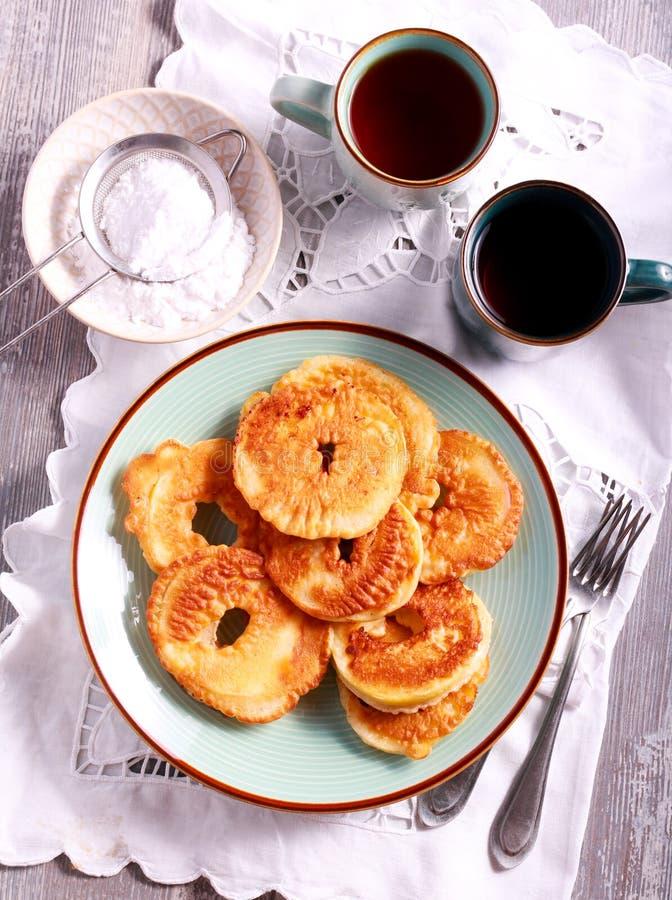 Fritters της Apple στο πιάτο και τα φλυτζάνια του τσαγιού στοκ εικόνα