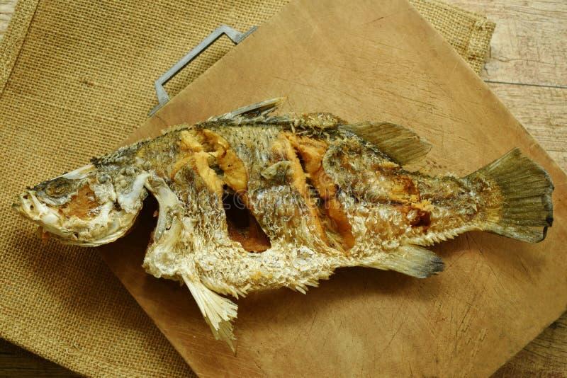 frittierte salzige Bass-Fische auf hölzernem Hiebblock lizenzfreies stockbild