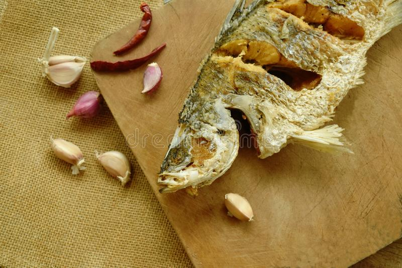 Frittierte salzige Bass-Fische mit Knoblauch und Paprika auf hölzernem Hiebblock stockfotografie
