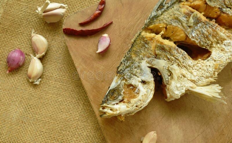Frittierte salzige Bass-Fische mit Knoblauch und Paprika auf hölzernem Hiebblock lizenzfreie stockfotos
