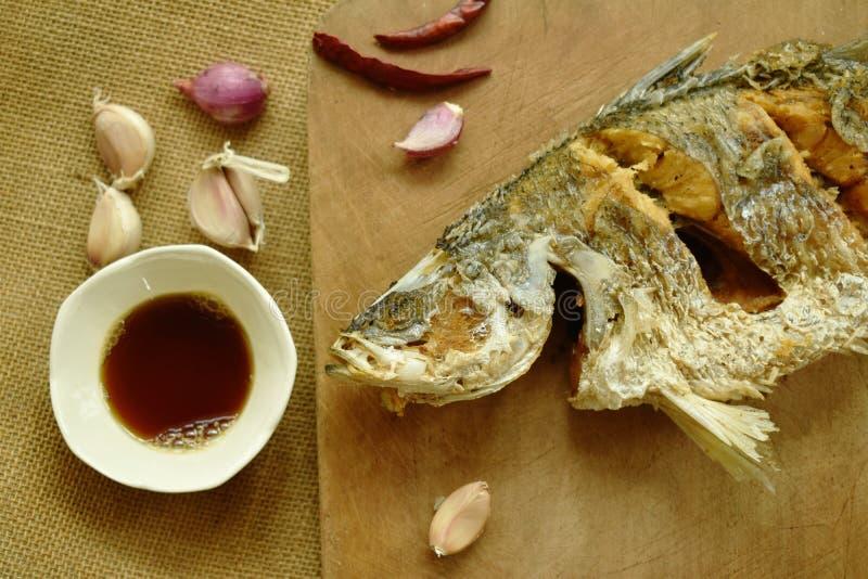 Frittierte salzige Bass-Fische mit Sojasoße auf hölzernem Hiebblock stockfotos