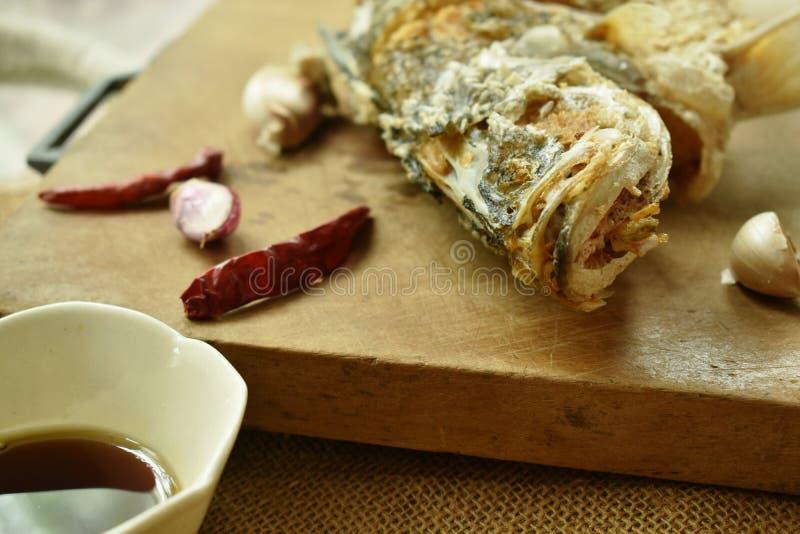 Frittierte salzige Bass-Fische mit Sojasoße auf hölzernem Hiebblock stockfoto
