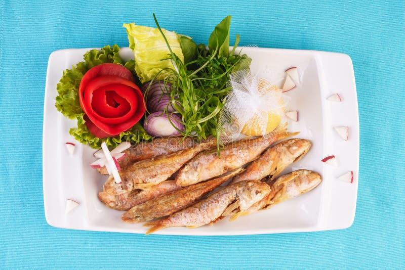 Frittierter Fisch in tiefem Fett, Lodde in Teig mit Grün, Tomaten, Käse und roten Zwiebeln lizenzfreies stockfoto