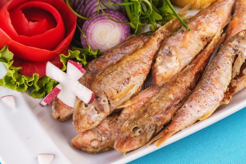 Frittierter Fisch in tiefem Fett, Lodde in Teig mit Grün, Tomaten, Käse und roten Zwiebeln lizenzfreies stockbild