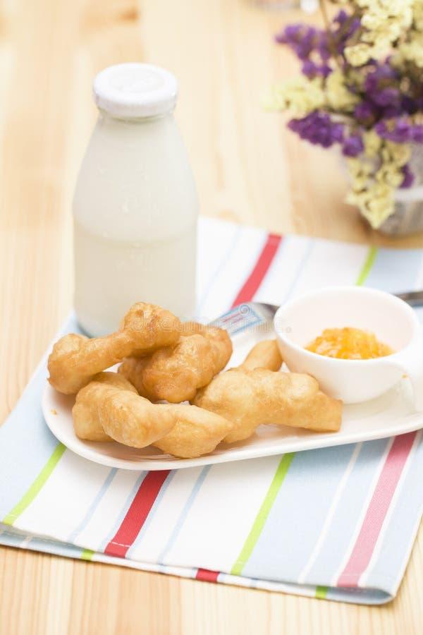 Frittiertes doughstick mit Orangenmarmelade und eine Flasche Milch lizenzfreie stockfotografie