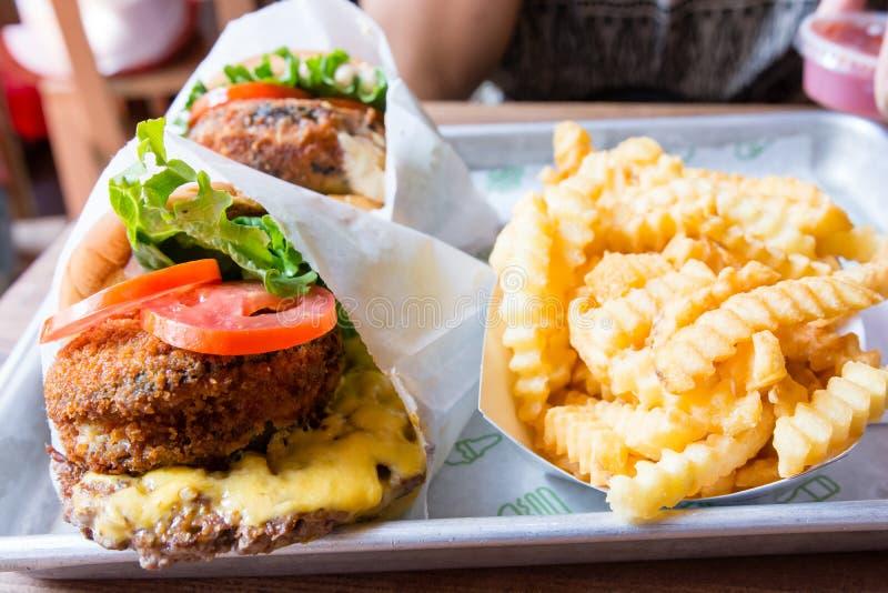 Fritture del taglio dell'hamburger e della mano della pila di Shack fotografia stock libera da diritti
