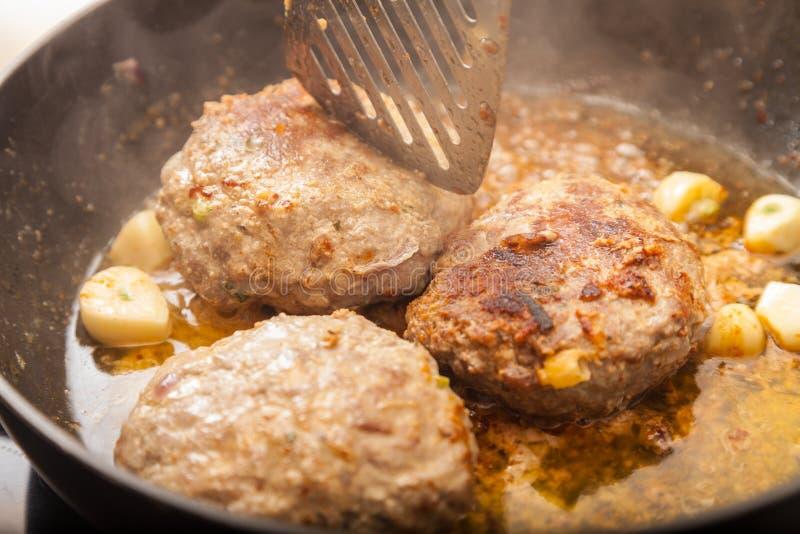 Fritture dell'hamburger della carne in una pentola immagine stock libera da diritti