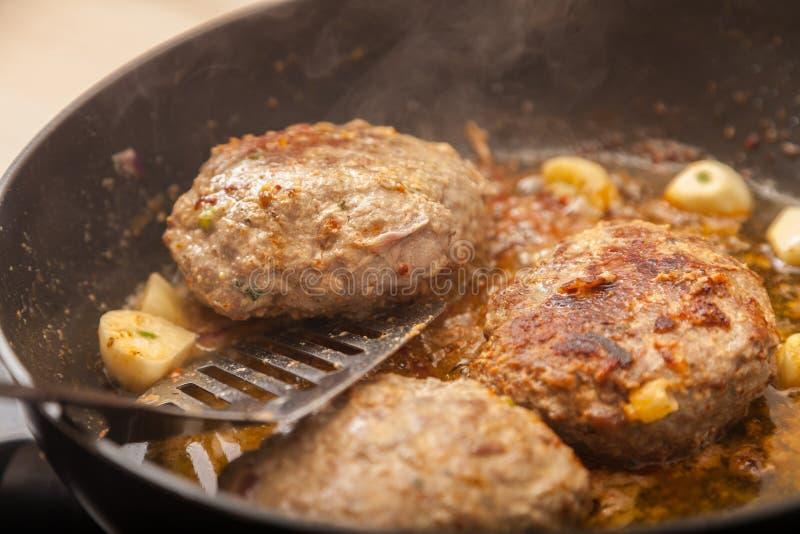 Fritture dell'hamburger della carne in una pentola fotografie stock libere da diritti