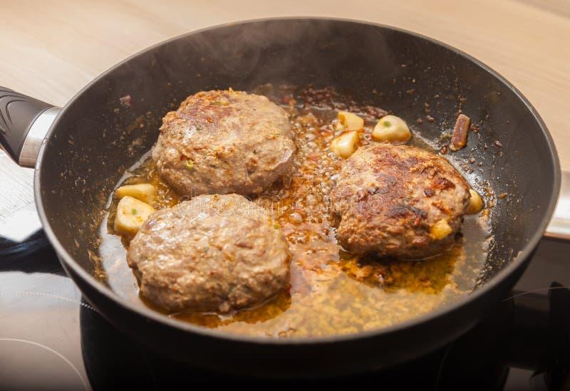 Fritture dell'hamburger della carne in una pentola fotografia stock