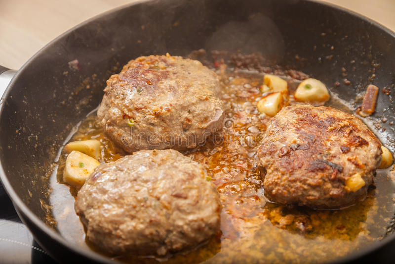 Fritture dell'hamburger della carne in una pentola immagine stock