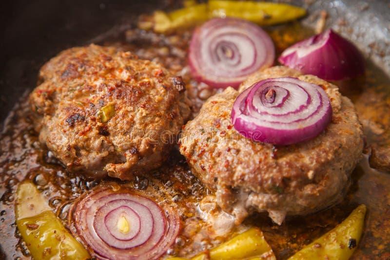 Fritture dell'hamburger della carne in una pentola immagini stock