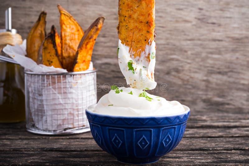 Fritture della patata dolce in involucro di carta eseguito nel canestro del servizio del metallo con il souce crema fresco della  fotografie stock