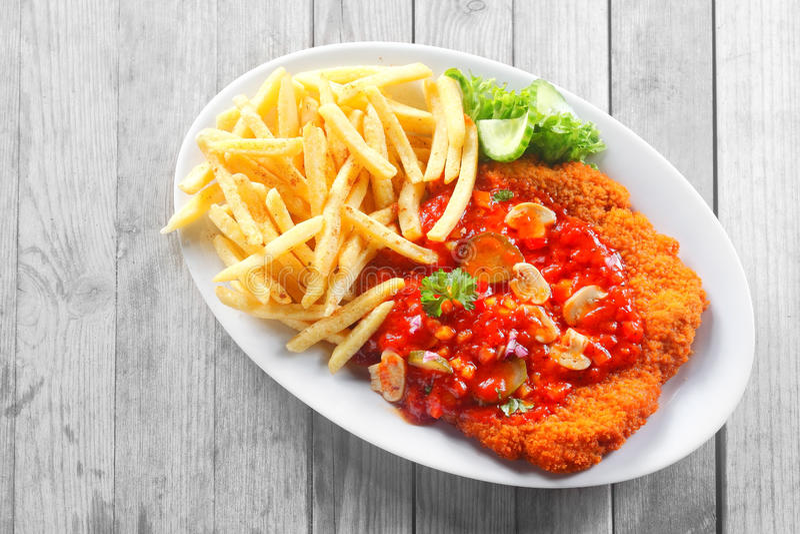 Fritture gastronomiche della patata e scaloppina impertinente sulla Tabella fotografia stock libera da diritti