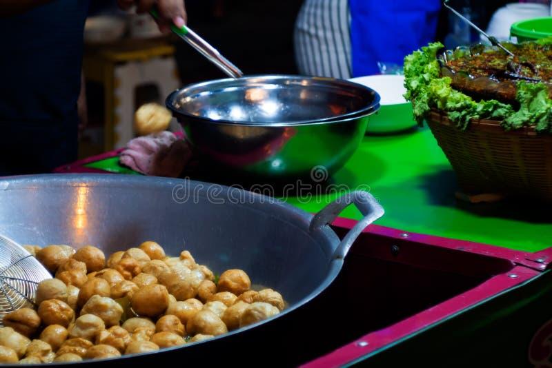 Friture de boule de poissons dans une poêle avec de l'huile chaude en nourriture de rue de la Thaïlande photos libres de droits