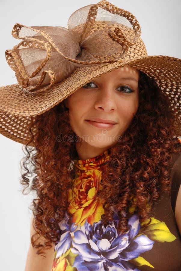 Frizzy Mädchen im Hut breit-geströmt. lizenzfreie stockfotos