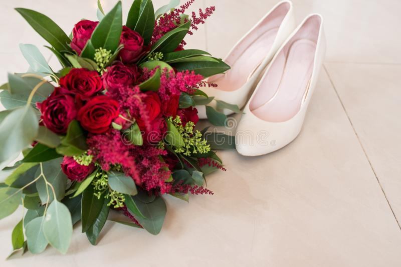 Frodig brud- bukett av röda rosor och mycket grönska med eleganta brud- skor bröllop arkivfoto