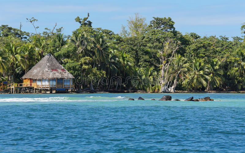 Frodig tropisk kust med den halmtäckte bungalowen Panama royaltyfri fotografi