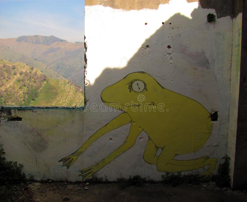 Frog in the bunker. Moro Mountain, Genoa, Italy. Second World War bunker, a graffiti and a window with a country landscape. Inside and outside, nature and stock photos
