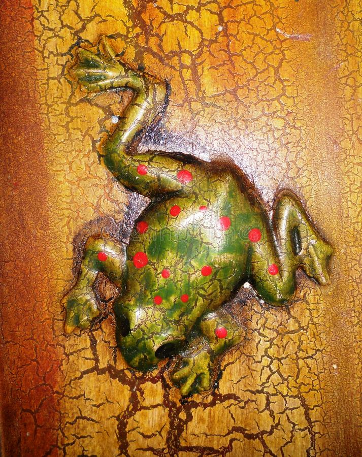 The frog paints. The beautiful brass frog is green with red dots, has its long hind legs, is on a beautiful base of brass, yellow with orange stock images