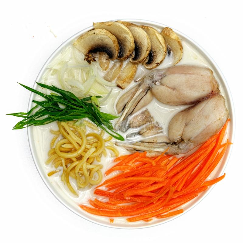 frog soup, carrots, noodles, onions, mushrooms with seafood, calamari, shrimps in a plate on white background top view stock photography