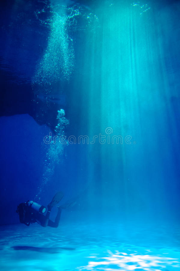 Frogman in water. Frogman diving under water searching for marine life stock photo