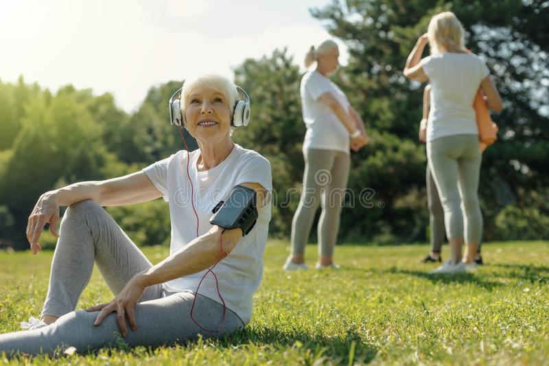 Frohe ältere Dame, die Musik nach Eignungstraining hört lizenzfreie stockfotografie