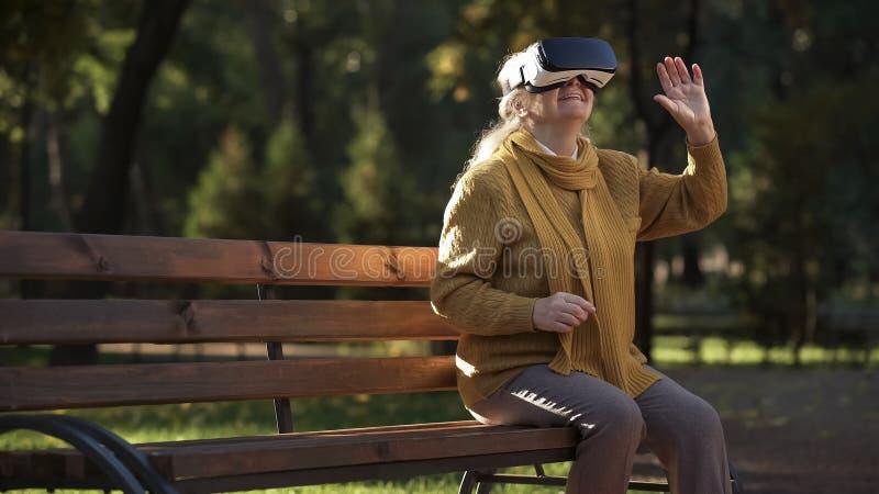 Frohe ältere Dame unter Verwendung vr Kopfhörers, der auf Bank im Park, Unterhaltung sitzt stockfoto