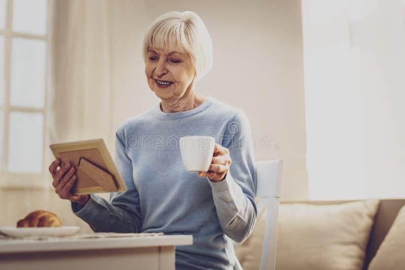 Frohe ältere Frau, die das Foto betrachtet stockfotos