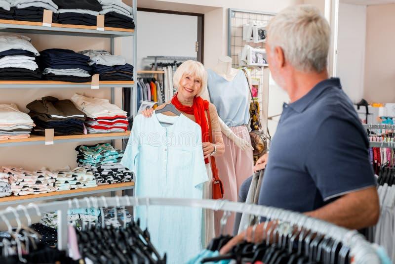 Frohe ältere Frau, die dem Verkäufer ein Kleid zeigt stockfotos