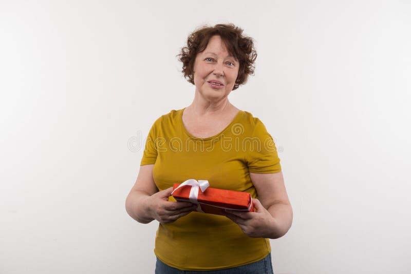 Frohe ältere Frau, die ein Geschenk hält stockfoto