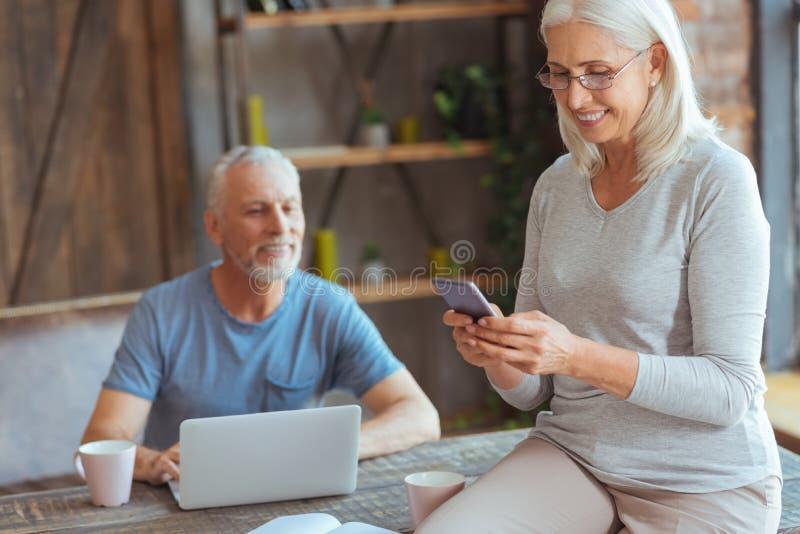 Frohe ältere Frau, die ihr intelligentes Telefon verwendet stockfotografie